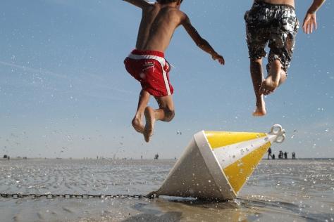 Zwei Kinder springen in St. Peter-Ording am Strand bei Niedrigwasser über eine Positionstonne