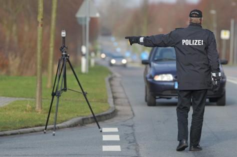 Polizist winkt ein PKW heraus bei einer Geschwindigkeitsmessung mit einem Lasergerät TraffiPatrol, Modell Traffipax der Fa. Jenoptik